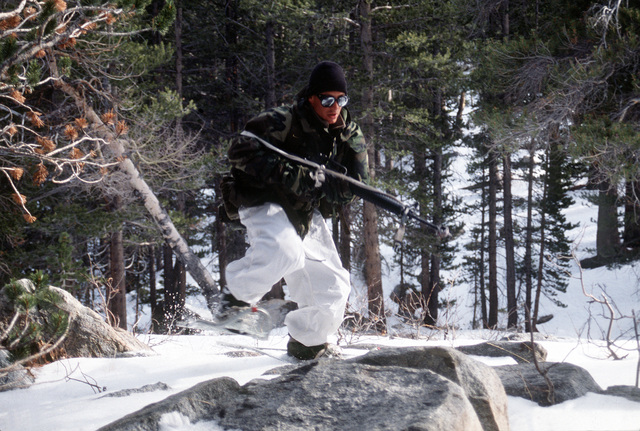 While on an ambush patrol, a Marine rifleman from India Company, Third Battalion, Eighth Marines rushes across snow covered rocks into the kill zone carrying an M16A2 rifle to assault an objective during cold weather training at Silver Creek