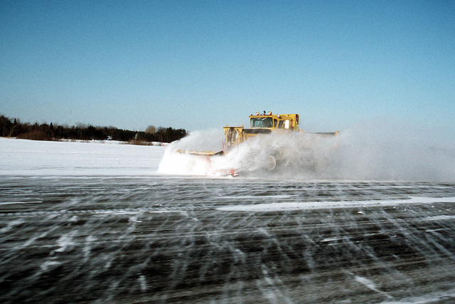 A snow plow is busy clearing the main runway at Naval Air Station Brunswick following a snow storm