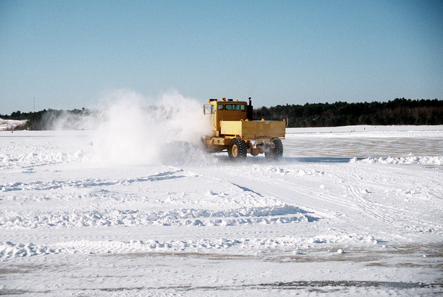 A snow plow is busy helping to clear the main runway of snow following the morning winter snow storm. Patrol Wing Five (VPW-5) operates numerous P-3C Orion patrol squadrons from this base and the aircraft must be ready to fly regardless of the weather