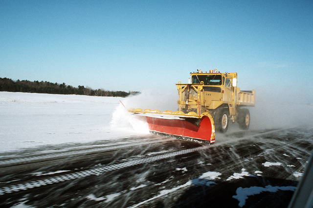 As the sky clears out from the past evenings snow storm, snow plows begin clearing the runways at Naval Air Station Brunswick so flight operations can continue