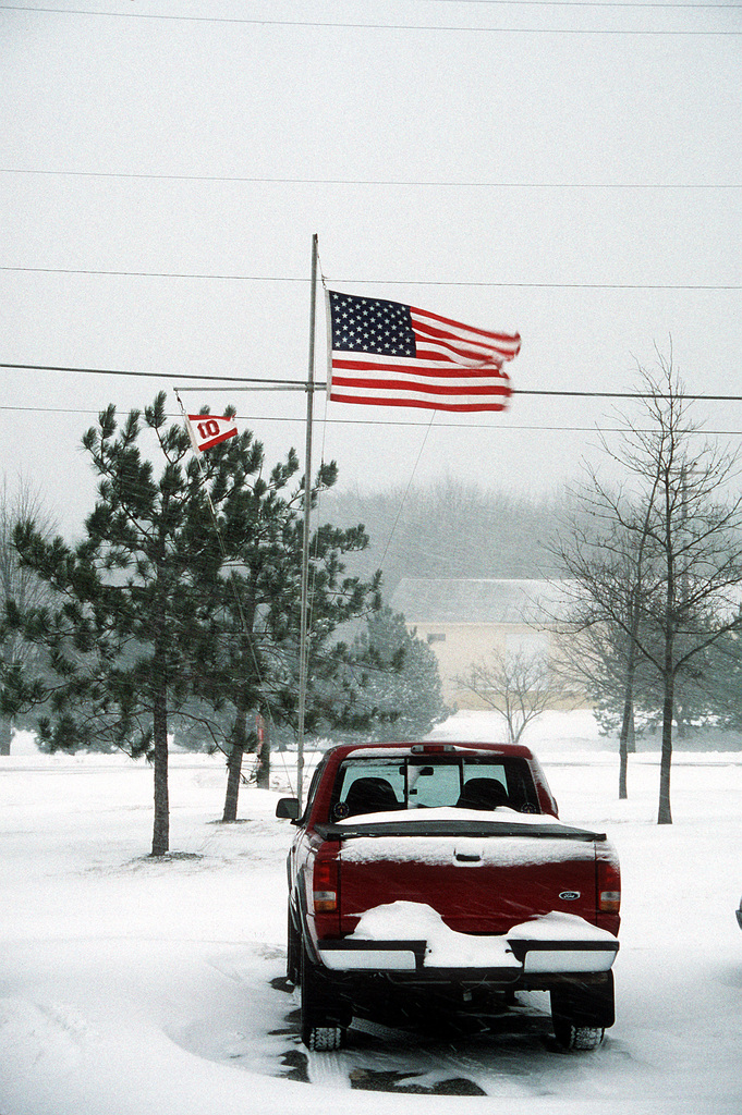 The wind whipped National ENSIGN flys over Naval Air Station Brunswick during a winter storm