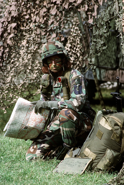 "MASTER SGT. Frazier, dressed in camouflage fatigues, camouflage paint and combat helmet is kneeling down beside her weapon and backpack holding a map. Department of Defense has announced a change which could open thousands of combat support jobs to military women. The change was announced by Defense Secretary Les Aspin to give a new standard definition for direct ground combat and the elimination of the Department of Defense's ""risk rule"" effective October 1994"