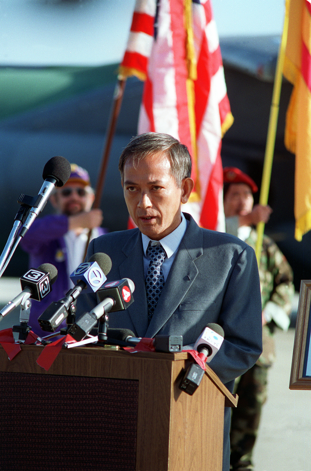 Former South Vietnamese Air Force helicopter pilot stands at the podium on the flight line as he delivers a speech before two hundred well wishers. MAJ Nquyen Quy An risked his life to save four American soldiers in a sniper-filled jungle in Laos, and for his heroism that day. An received the Distinguished Flying Cross