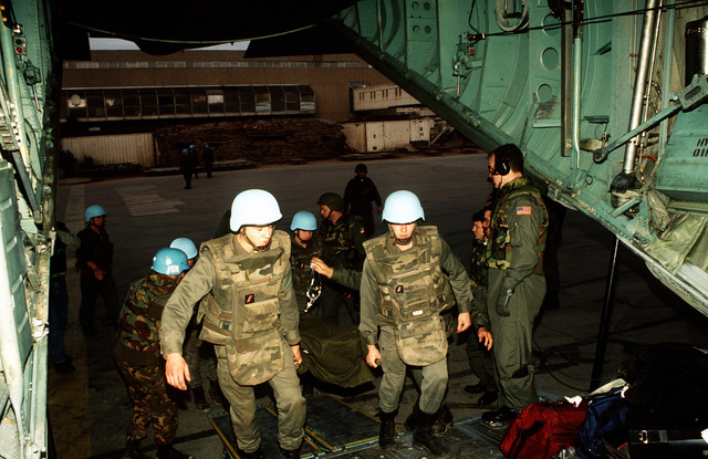 French soldiers place a wounded Bosnian inside a C-130 waiting to leave for Ramstein AB, Germany. Once at Ramstein the wounded were transported by medical bus to the Army Regional Medical Center in Landstuhl