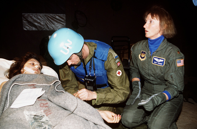 MAJ. Judy Young, Nurse, 2nd Aero Medical Evacuation Squadron assists a Norwegian UN medic administer an IV. On Saturday, Feb. 5 just after noon, an exploding mortar round hit the Markale market killing more than 63 people and wounding 206 others. At the request of the United Nations, aircraft from Rhein-Main AB, Germany, and the International Red Cross were sent in to Sarajevo to airlift the wounded to Ramstein AB, Germany. Once at Ramstein the wounded were transported by medical bus to the Army Regional Medical Center in Landstuhl