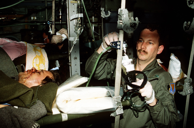 Members from the 2nd Aero Medical Squadron place the wounded patient on their appropriate stanchions inside the C-130. At the request of the United Nations, aircraft from Rhein-Main AB, Germany, and the International Red Cross were sent in to airlift the wounded to Ramstein AB, Germany. Once at Ramstein the wounded were transported by medical bus to the Army Regional Medical Center in Landstuhl