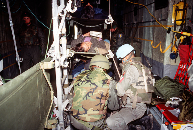 Two camouflaged Air Force Aircrew members situate Medivac patients aboard the C-130. An exploding mortar round hit the market killing 63 people and wounding 206 others. At the request of the United Nations, aircraft from Rhein-Main AB, Germany, were sent into Sarajevo to airlift the wounded to Ramstein AB, Germany. Once at Ramstein AB, Germany the wounded were transported by medical bus to the Army Regional Medical Center in Landstuhl