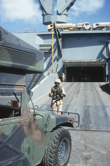 U.S. Army soldier from the 155th Transportation Company, Fort Eustis, VA, guides heavy motor transport aboard the USNS Denebola