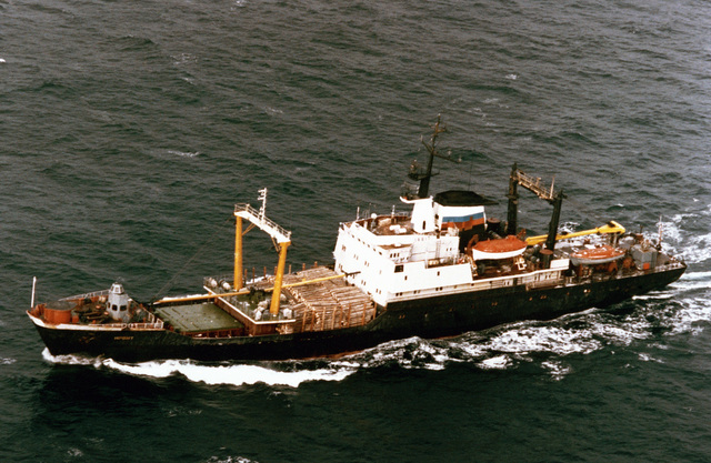A port side view of the Russian Navy Pacific Fleet Neon Antonov class cargo ship IRBIT underway with a commercial cargo of logs