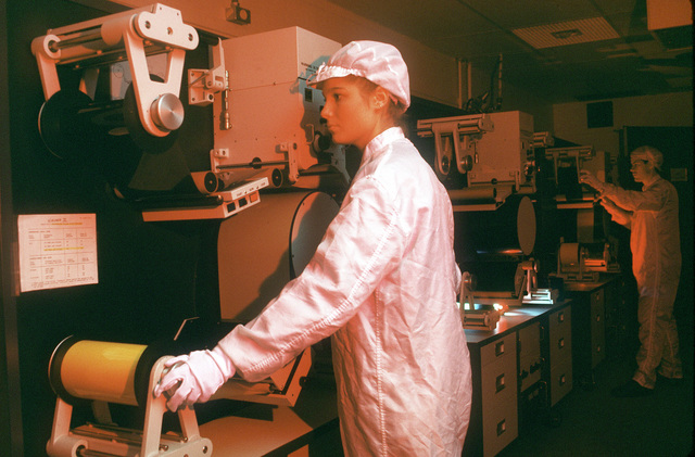 """Outfitted in lab coats, jump suits, hats and gloves, in order to maintain a clean lab environment, the """"select print"""" crew members use a Niagara III continuous printer to print the required images from the U-2R reconnaissance films for the tasking customer. Exact Date Shot Unknown . Published in AIRMAN Magazine, May 1994"""