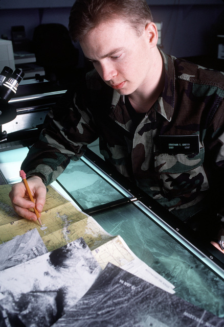 The first print copy of the U-2R reconnaissance imagery is delivered to photo interpreter STAFF SGT. Jonathan Griffin who matches the print to the map of the mission. Exact Date Shot Unknown . Published in AIRMAN Magazine, May 1994
