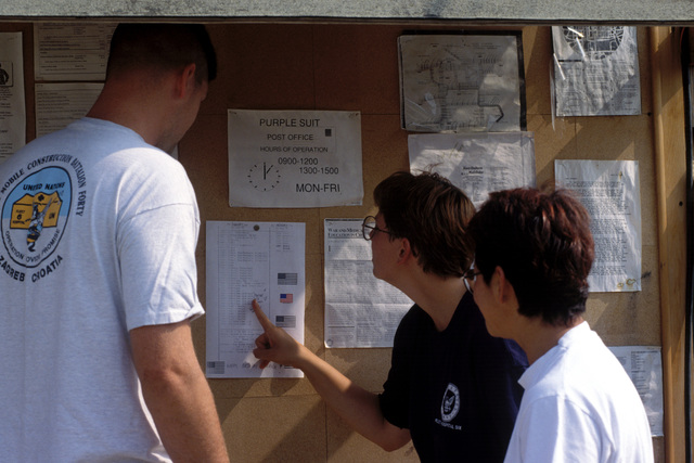At the Town Square some look to see what the days schedule of events are for the Independence Day celebration at Camp Pleso