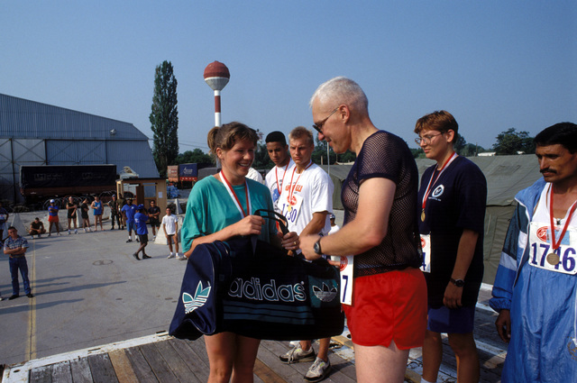 COL. Burton C. Quist, commander Joint Task Force Provide Promise (Forward), US Marine Corps, presents a gym bag to Sue Stockdale, Quality Assurance Officer, Headquarters United Nations Protective Forces for her performance in the Independence Day 5K Fun Run at Camp Pleso