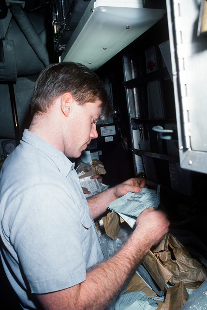 Machinist Mate Second Class (MM2) Richard Villnave checks the certification of the pumping on a sanitary tank in the galley of the nuclear-powered submarine USS MIAMI (SSN-755) during a routine overhaul period