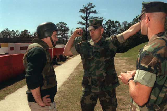 Undersecretary of Navy Richard Danzig is instructed how to properly throw a M-67 fragment grenade by SGT. Karn of Weapons Battalion, Marine Corps Recruiting Depot, Parris Island, SC