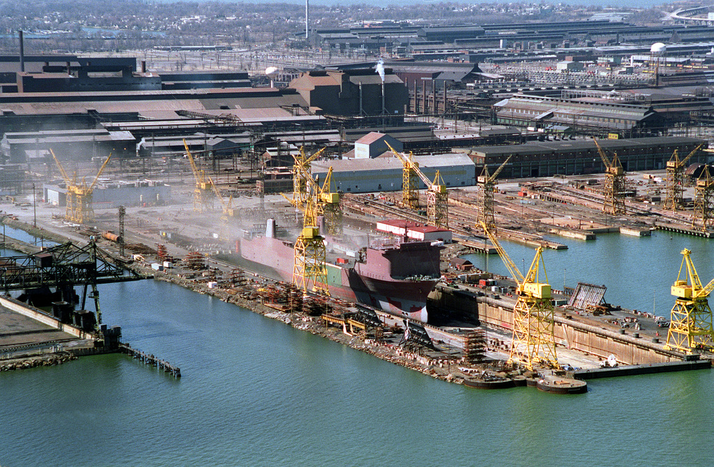 A port quarter view of the aircraft carrier CORAL SEA (CV-43) moored at the Baltimore Fairfield Terminal for scrapping by the Seawitch Marine Salvage Company. Large portions of the armored flight deck have already been removed exposing the interior of the hangar bay