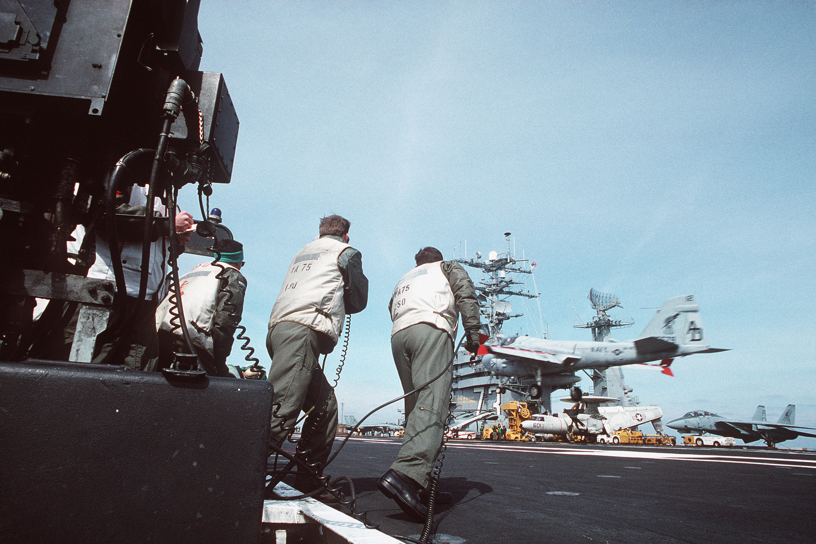 The Landing Signal Officers (LSO) of Attack Squadron Seventy-Five (VA-75) watch as one of the squadrons A-6E Intruder aircraft settles down on the flight deck during recovery (landing) operations as part of carrier qualifications on board the nuclear-powered aircraft carrier USS George Washington (CVN-73)
