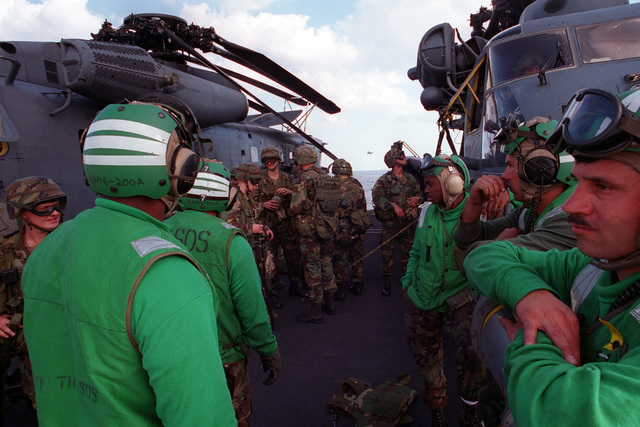Flight deck personnel of the nuclear-powered aircraft carrier USS GEORGE WASHINGTON (CVN-73) standby as U.S. soldiers of the 75th Special Forces Group (Airborne) prepare to embark in U.S. Air Force MH-53J combat search and rescue helicopters during Fleet Exercise 2-94