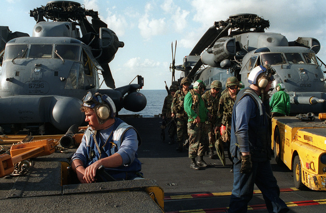 Flight deck personnel of the nuclear-powered aircraft carrier USS GEORGE WASHINGTON (CVN-73) standby as soldiers of the 75th Special Forces Group wait to board U.S. Air Force MH-53J combat search and rescue helicopters during Fleet Exercise 2-94