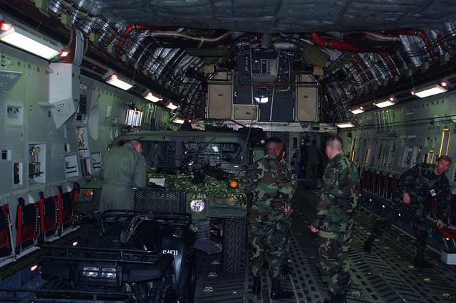 Interior view looking forward in the cargo bay of the new USAF C-17 Globemaster III transport aircraft showing the loading of U.S. Marine Corps vehicles including an M998 High-Mobility Multipurpose Wheeled Vehicle (HMMWV) during a joint service loading test of the new aircraft