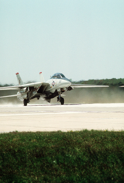 A right front view of an F-14A Tomcat aircraft of Fighter Squadron 41 (VF-41) lifting off runway 05 carrying Mark 76 practice bombs for a training sortie flight over the Dare County Bombing Range