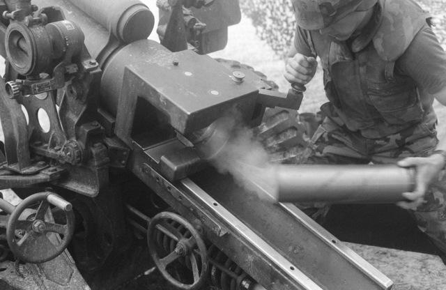 A Marine artilleryman removes a spent round from the breech of an M114 155 Howitzer
