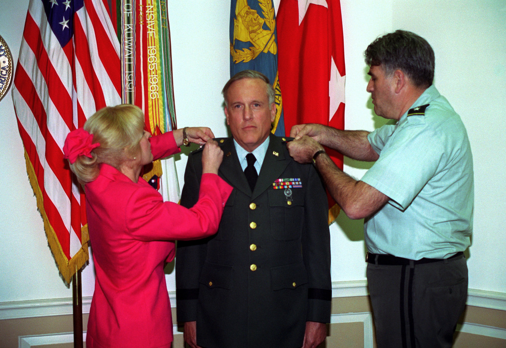 MGEN Max Baratz (right), Acting CHIEF, U.S. Army Reserve, promotes BGEN George Kundahl to the rank of major general. MGEN Kundahl's wife Joy assists during the promotion ceremony