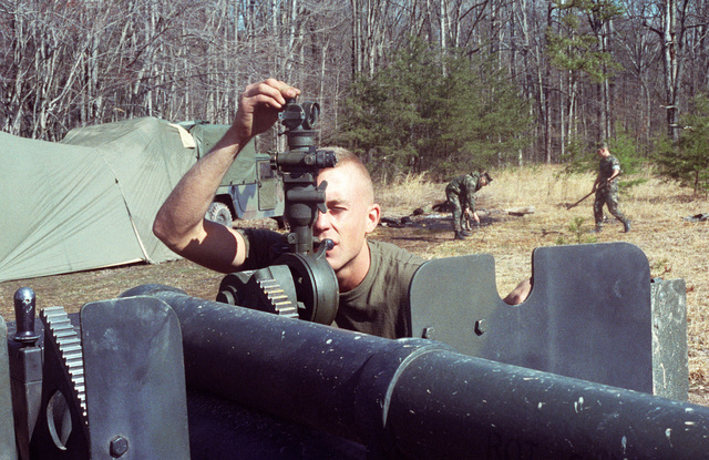 A Marine artillerymen enters a target solution on the sight device of his M114 155 Howitzer