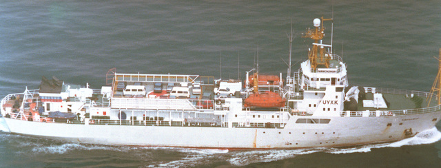 An aerial starboard side view of the Russian Ministry of Fisheries protection ship MANCHZHUR underway with a deck load of passenger vehicles