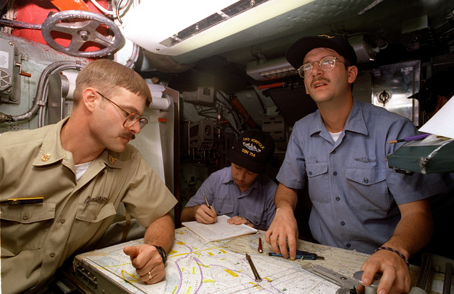 CHIEF Electronics Technician (ETC) Dean Key, Electronics Technician Third Class (ET3) Kenneth Messier and Electronics Technician Third Class (ET3) Thomas Butcher review charts aboard the nuclear-powered attack submarine USS NORFOLK (SSN-714) as the ship prepares to get underway for Annapolis, MD