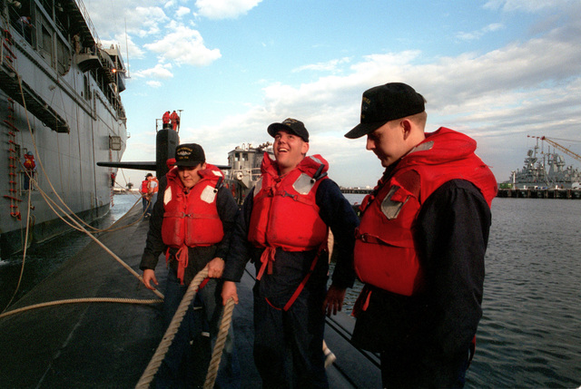 (Left to right) An unidentified interior communications electrician third class (IC3), Mess SPECIALIST SEAMAN (MSSN) Gregory Ginther and Torpedoman SEAMAN (TMSN) Peter Jaquez of the nuclear-powered attack submarine USS NORFOLK (SSN-714) prepare to get underway from alongside the submarine tender USS EMERY S. LAND (AS-39) which is moored at the destroyer and submarine (D&S) piers at the Norfolk Naval Base. The large harbor tug WAPAKONETA (YTB-766) (behind the sailors) is alongside to assist the sub in getting underway