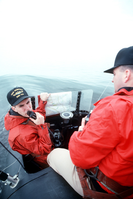 LTJG. Drew Rainer communicates on the 1MC radio link as he and LCDR Tim Mulcare stand the maneuvering watch on the sail of the nuclear-powered attack submarine USS NORFOLK (SSN-714)