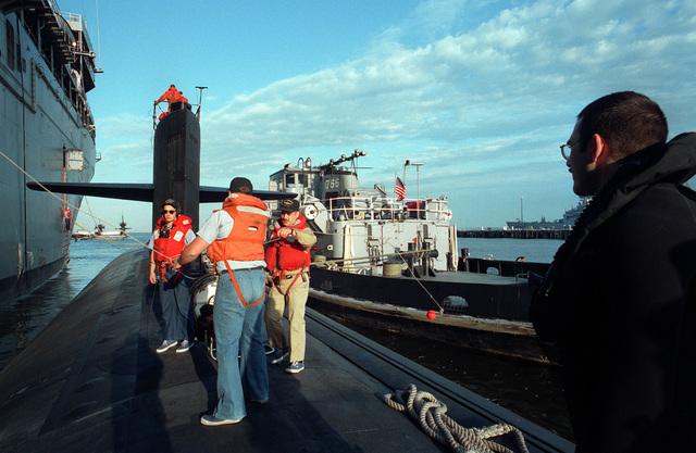 Members of the deck force as the nuclear-powered attack submarine USS NORFOLK (SSN-714), are shown preparing to get underway from alongside a submarine tender at the Norfolk Naval Base. The large harbor tug Wapokoneta (YTB-766) is alongside to the right to assist the Norfolk in getting underway