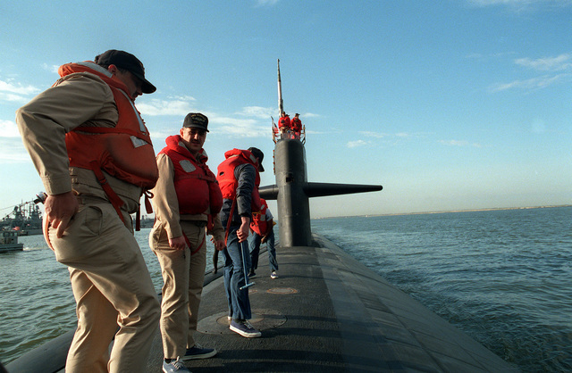 Members of the deck force of the nuclear-powered attack submarine USS NORFOLK (SSN-714), are shown on the bow of the ship as the vessel departs the Norfolk Naval Base for Annapolis, MD