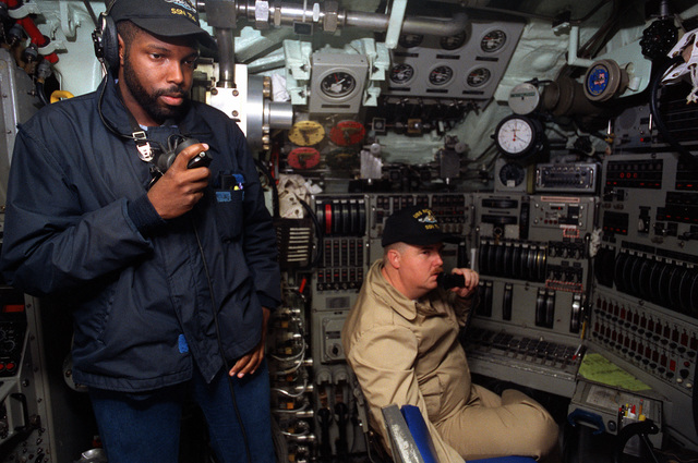 SENIOR CHIEF Torpedoman (TMCS) Jeffery Leonard mans the communication console in the control room of the nuclear-powered attack submarine USS NORFOLK (SSN-714) as one of the crew operates the sound-powered telephone link to the maneuvering watch on the sail