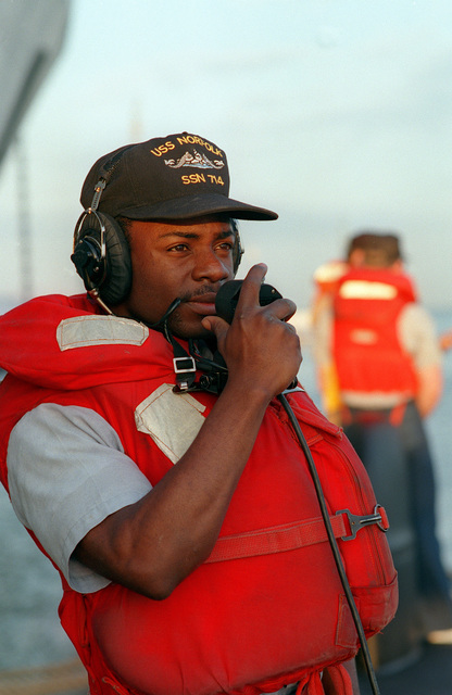 Sonar Technician Second Class (ST2) Kenneth Elmore serves as part of the deck force on the sound-powered telephone aboard the nuclear-powered attack submarine USS NORFOLK (SSN-714) as the ship prepares to get underway for Norfolk Naval Base for Annapolis, MD