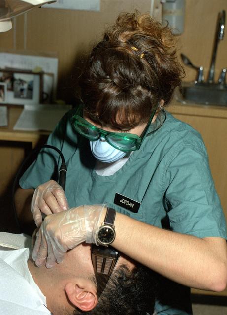 Dentalman (DNSN) Sybil J. Jordan gives Machinist Mate Second Class (MM2) George Pharo a teeth cleaning on board the submarine tender USS HOLLAND (AS-32)