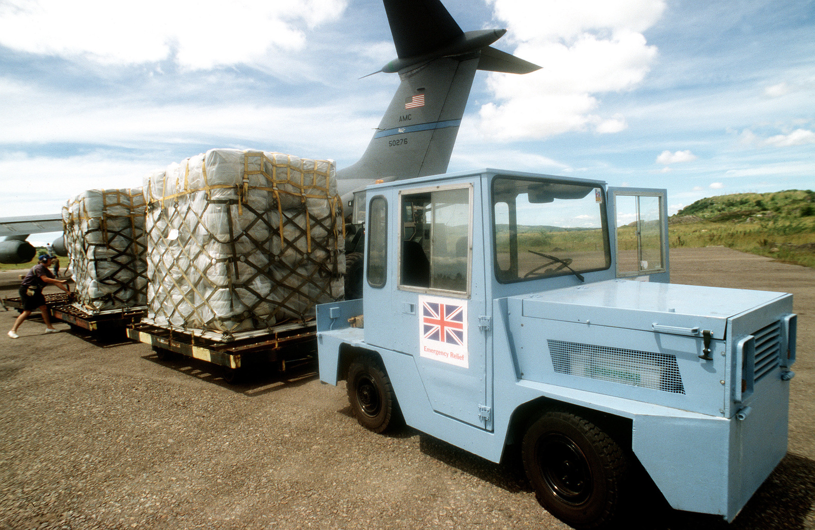 A British lightweight vehicle pulls two pallets of supplies after being off load from a C-141B from the 438th Airlift Wing, McGuire Air Force Base, NJ