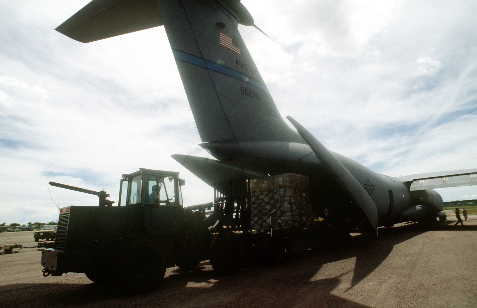 A forklift off loads a C-141B from the 438th Airlift Wing, McGuire Air Force Base, NJ