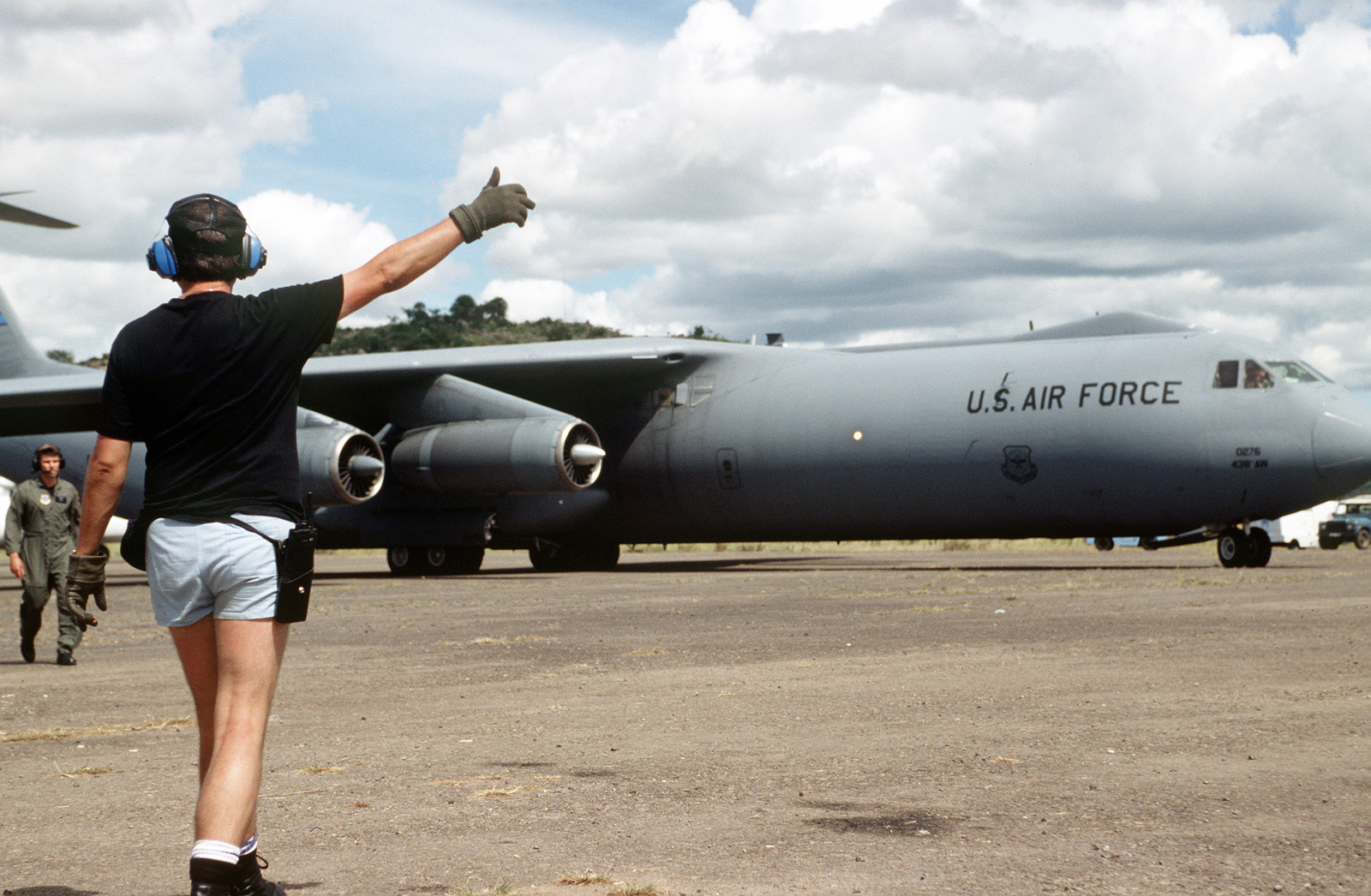 A ground crewmember directs a C-141B from the 438th Airlift Wing, McGuire Air Force Base, NJ, to a parking area on the flightline