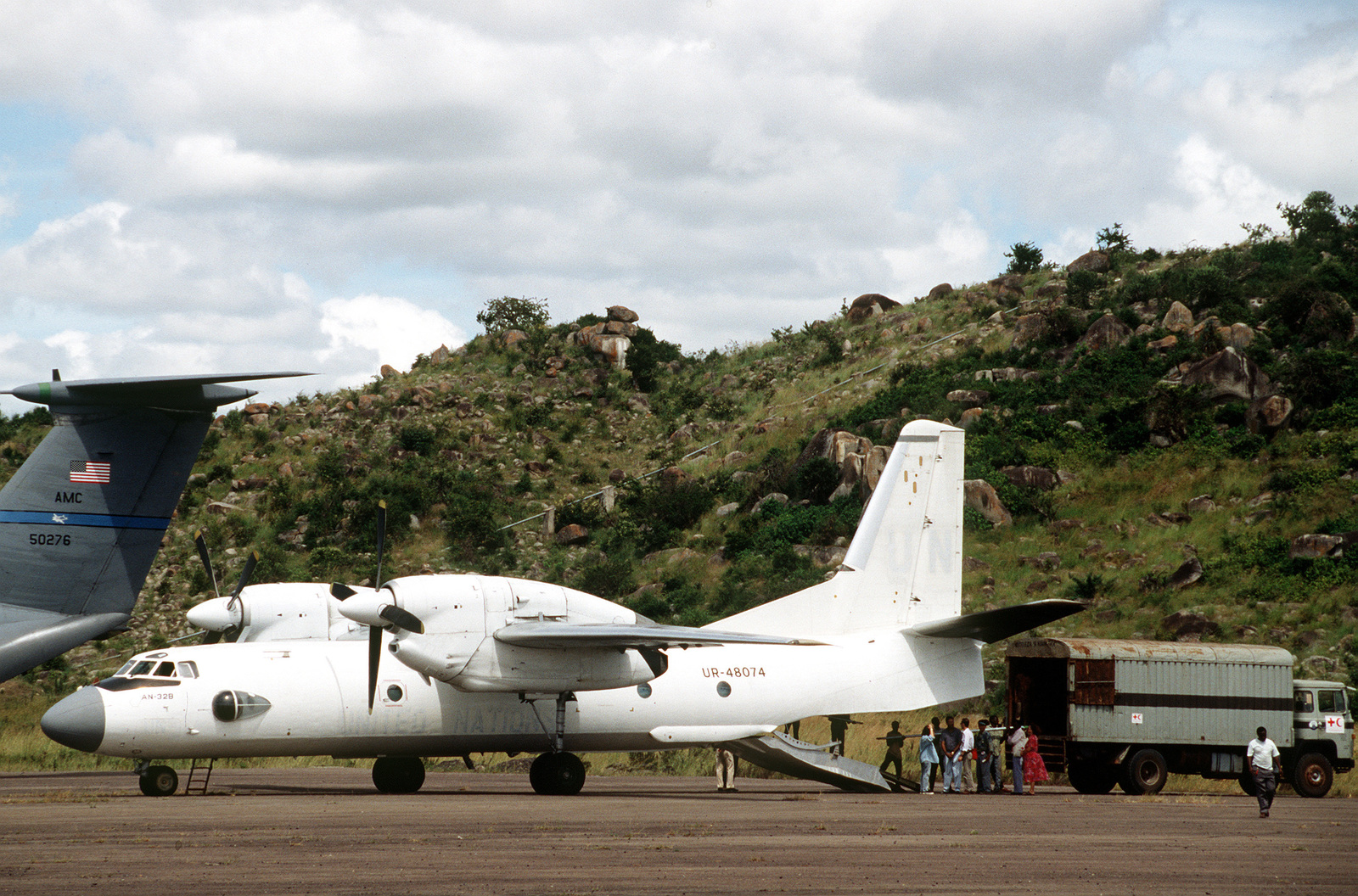 A left side view of an AN-32 Cline Russian aircraft being used by the Red Cross during the airlift