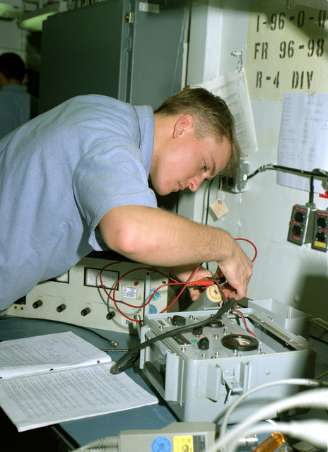 Electronic Technician Third Class (ET3) Gregory S. Sipes hooks up equipment for calibration on board the submarine tender USS HOLLAND (AS-32)