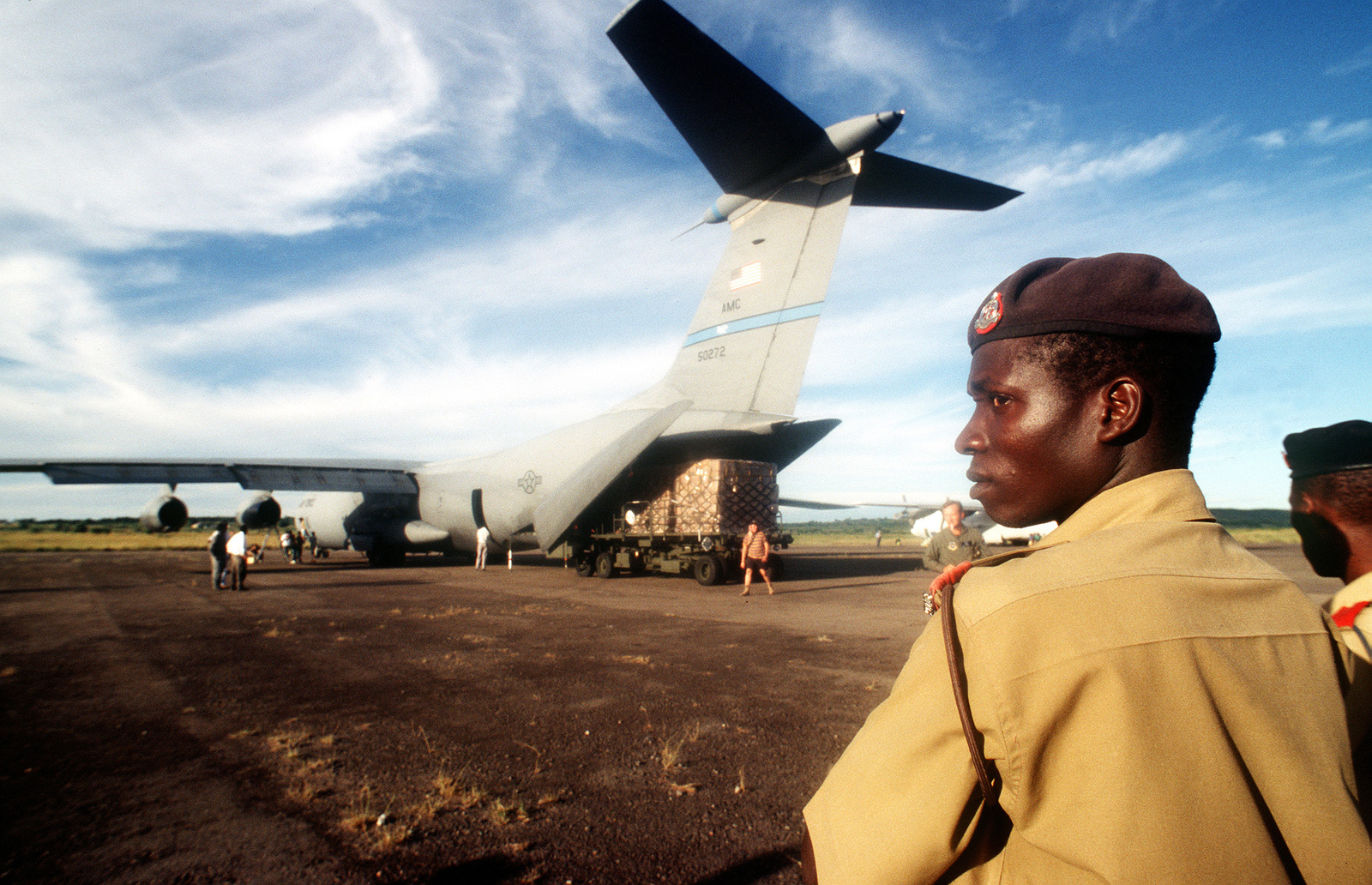 Local military personnel stand watch as unidentified personnel off load supplies from a C-141B. The aircraft is from the 438th Airlift Wing, McGuire Air Force Base, NJ