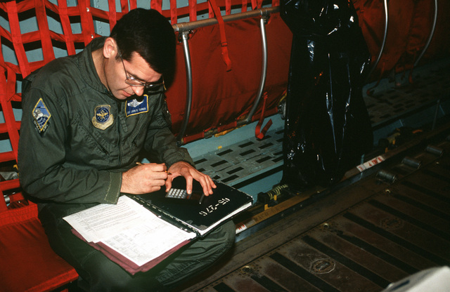 MASTER SGT. John W. Turner, loadmaster with the 18th Airlift Squadron (ALS), McGuire AFB, NJ, fills out forms prior to flight