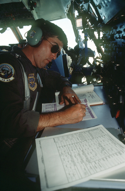 TECH. SGT. John H. Aldershoff, Flight Engineer, on the C-141B from the 438th Airlift Wing, McGuire Air Force Base, NJ, completes the aircraft usage log while in flight