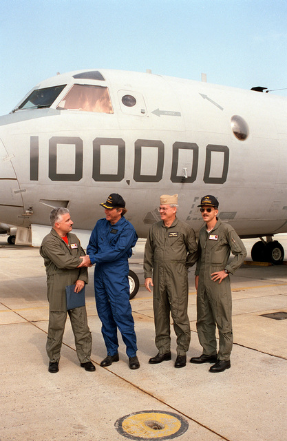 CDR. E. Bryon Fisher, Jr., commanding officer of Patrol Squadron 68 (VP-68), shakes hands with the Honorable Wade R. Sanders, Deputy Assistant Secretary of the Navy (Reserve Affairs) upon completion of a training flight which marked 100,000 mishap free flight hours flown by air crews of Patrol Squadron 68 (VP-68), the Black Hawk (Blackhawk)s, On Mr. Sanders left is CDR. Robert A. Sinbaldi, Jr., VP-68's executive officer and a unidentified commander. Secretary Sanders had accompanied the air crew on the historic flight in the P-3C Update I Orion aircraft LW-00 shown in the background