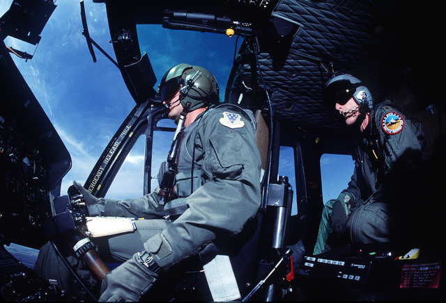 An upward angle of Helicopter Operations. Major Paul Bekebrede is watching CAPT Cowell pilot his UH1 To Kelo Zero. A joint Nuclear Surety Inspection was held. Inspectors from the Defense Nuclear Agency, Air Force Space Command and the Military Airlift Command joined forces to see how well Team Grand Forks ensured the safety, security and reliability of the nuclear resources under their command