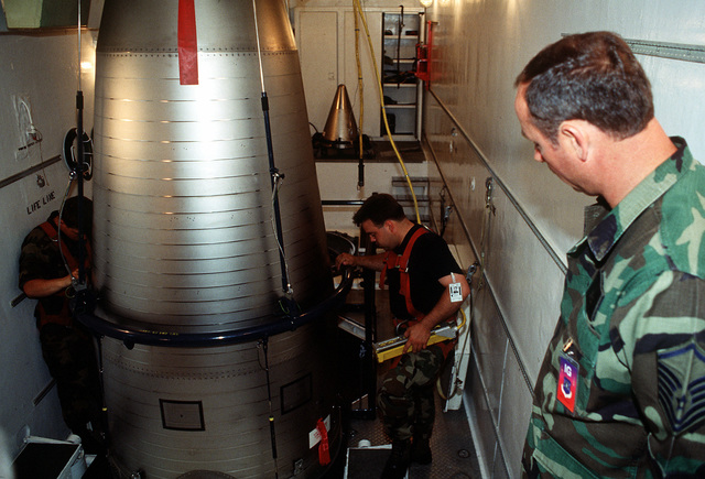 MASTER SGT. Ellis C. Hire, Space Command I.G. Inspector, observes STAFF SGT. Dennis Burdozski (right) and AIRMAN 1ST Class Edward Castel as they load a Minuteman Payload onto a PT Van transport to a launch facility. A joint Nuclear Agency, Air Force Space Command, and the Military Airlift Command joined forces to see how well Team Grand Forks ensured the safety, security and reliability of the nuclear resources under their command. The base passed with a satisfactory rating
