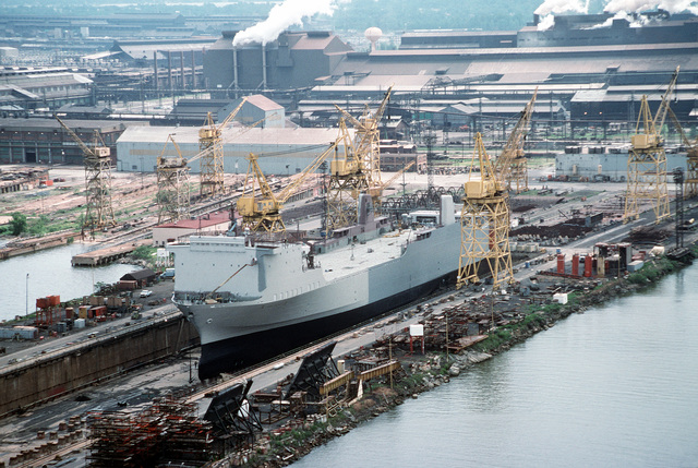 An aerial port bow view of the Military Sea Command (MSC) chartered vessel CAPE WRATH (T-AKR-9963) under overhaul and conversion in a dry dock at the Sparrows Point Extension Yard of the Bethleham Steel Corporation