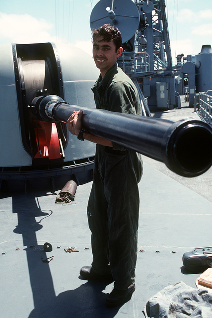 Gunners Mate Guns Third Class (GMG3) James Clark is shown assisting with the cleaning of the Mark 75 76mm OTO gunmount on board the guided missile frigate USS GARY (FFG-51)